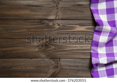 Purple napkin on the old wooden table. - stock photo
