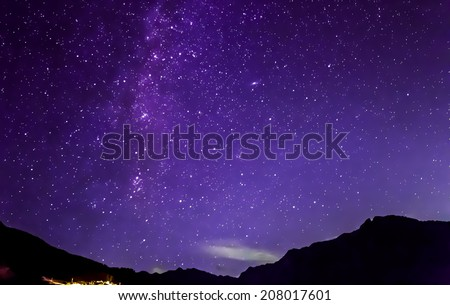 purple night sky stars and milky way over mountains - stock photo