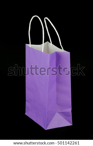 purple paper gift bag isolated on black background