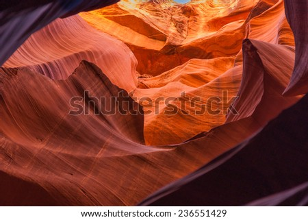 Purple, pink and orange swirling sandstone rock eroded by water in Upper Antelope Canyon located in Page, Arizona. - stock photo