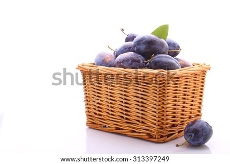 purple plums in a wicker basket on a white background