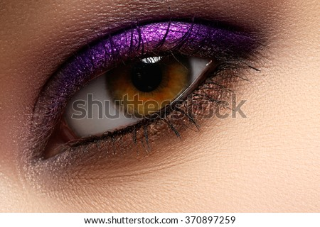 Purple shine make-up of woman eye. Woman eye with style violet and fashion make-up. Beautiful female face with bright purple fashion makeup - stock photo