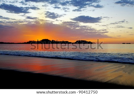 Purple skies and flowing water at sunset in Guanacaste - stock photo