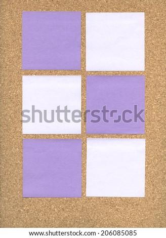 Purple sticky notes on a corkboard - stock photo