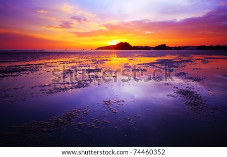 Purple sunset over a beach during low tide - stock photo