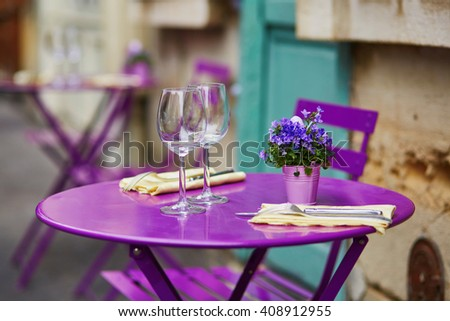 Purple table of Parisian outdoor cafe with wine glasses and flowers - stock photo