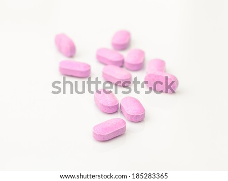 Purple tablets of medicine isolated on white. - stock photo