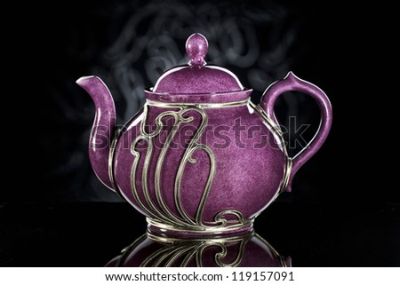 purple teapot with metal ornaments - stock photo