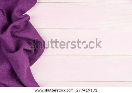 Purple towel over wooden kitchen table. View from above. - stock photo