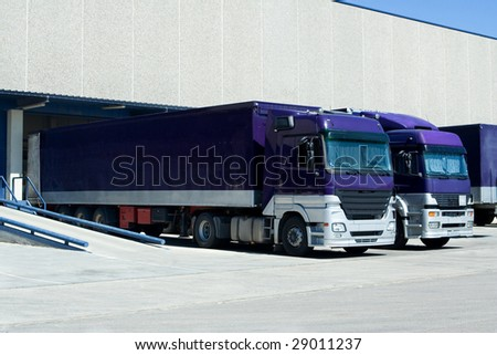 Purple Trucks Loading Goods at the Dock - stock photo