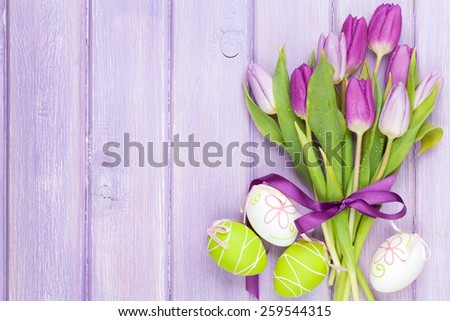 Purple tulip bouquet and easter eggs. Top view over purple wooden table - stock photo