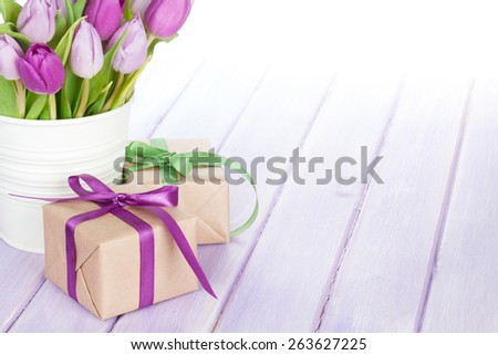 Purple tulip bouquet and gift box on wooden table with copy space - stock photo