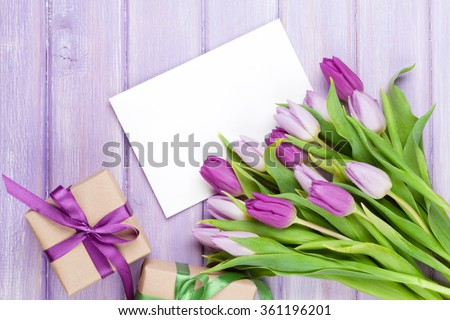 Purple tulip bouquet, blank greeting card and gift boxes. Top view over wooden table - stock photo