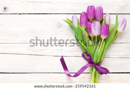 Purple tulip bouquet over wooden table with copy space - stock photo