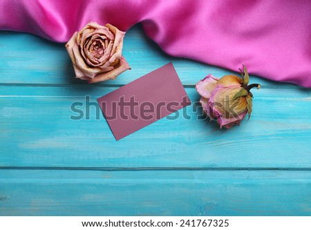 Purple wavy silk, dried roses and greeting card on blue wooden background. - stock photo