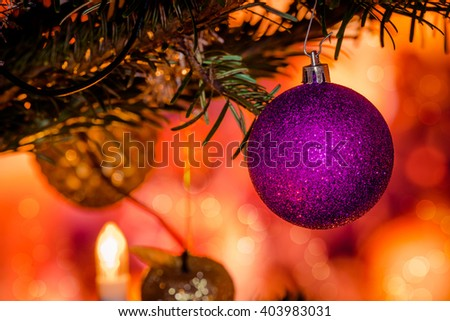 Purple Xmas bauble on a decorated Christmas tree - stock photo