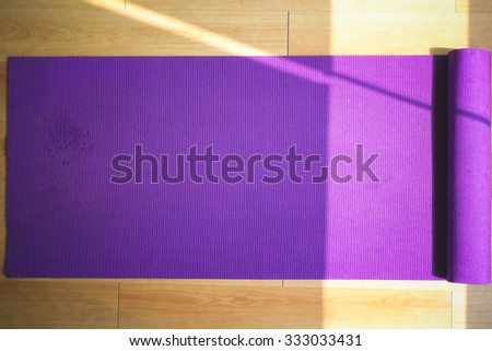 Purple yoga matt in empty gym. - stock photo