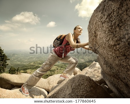 Purposeful hiker with backpack crossing rocky terrain - stock photo