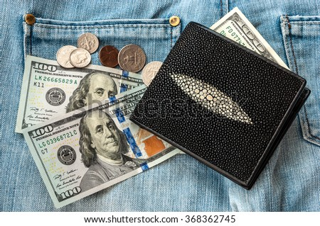 purse money. on jeans background.