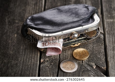 Purse with money on old rustic wooden table