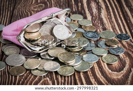 Purse with money on old rustic wooden table. Focus on the coins in the purse - stock photo
