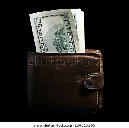 Purse with pack of dollars isolated on black.