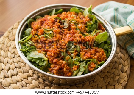 Purslane food with tomato sauce in a pan on a wicker at home on a wooden surface.
