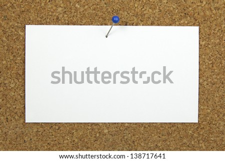push pin holding a blank note card on a cork board - stock photo