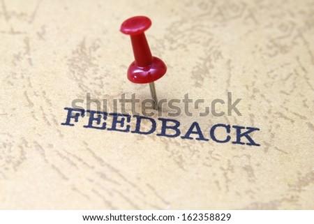 Push pin on feedback text - stock photo