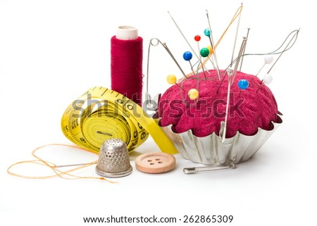 Push pins, safety pins, needles in pincushion, thimble and measuring tape - stock photo