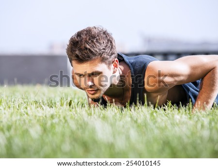 Push up muscular man on green lawn in city park - stock photo