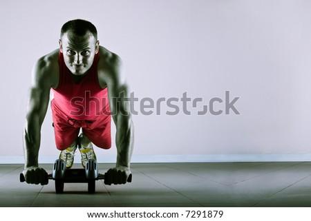 Push up with exercise wheel dramatization, classic endurance workout for biceps - stock photo
