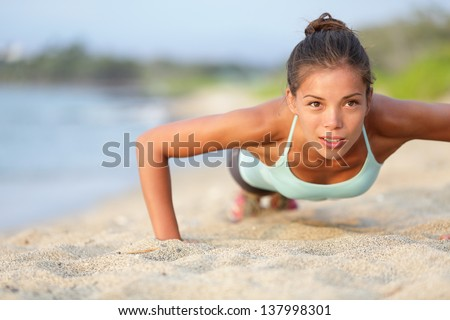 Push-ups fitness woman doing pushups outside on beach. Fit female sport model girl training crossfit outdoors. Mixed race Asian Caucasian athlete in her 20s. - stock photo