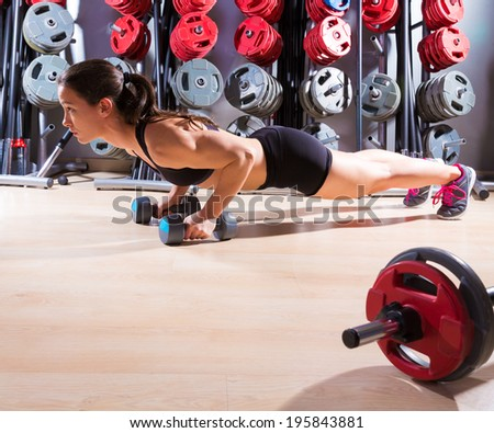 Push-ups woman with dumbbells workout fitness club at weightlifting gym - stock photo