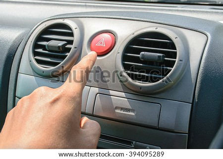 pushes car emergency lights button - stock photo