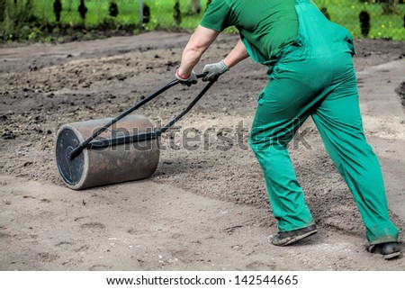 Pushing a lawn roller in a garden - stock photo