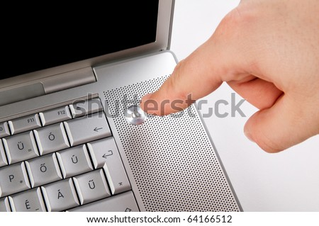 Pushing the Power Button on Laptop Computer - stock photo