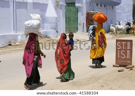 PUSHKAR, INDIA - JUNE 21: Local women carry their everyday load on their heads June 21, 2007 in Pushkar, India. Using a head is an efficient way to leave hands free for other luggage - stock photo