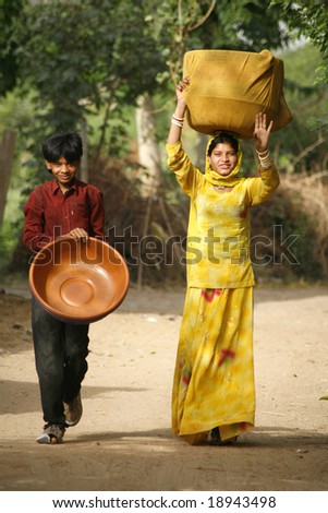 Pushkar, India - May 2008. Two young Rajasthani locals carrying containers for flower farming. - stock photo