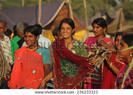 PUSHKAR, INDIA - NOV 28: Indian girls with traditional colored saree on the street of Pushkar during the Camel Fair exhibition on November 28 2012 - stock photo