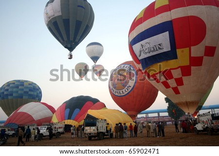PUSHKAR, INDIA - NOVEMBER 19: Crews ready hot air baloons for flight on November 19, 2010 at the Pushkar Camel Fair in Rajasthan, India.  The balloons fly over herds of camels for sale at the fair.