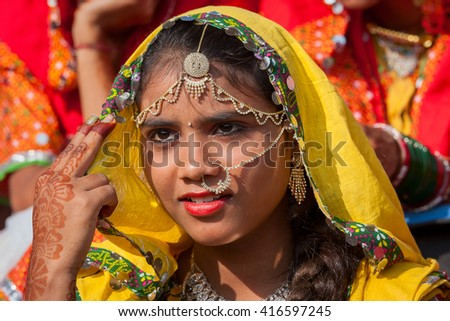 PUSHKAR, INDIA - NOVEMBER 21, 2012 : Portrait of Indian girl in colorful ethnic attire at Pushkar Camel Mela in Rajasthan, India. Pilgrims and camel traders flock to the holy town for the annual fair. - stock photo