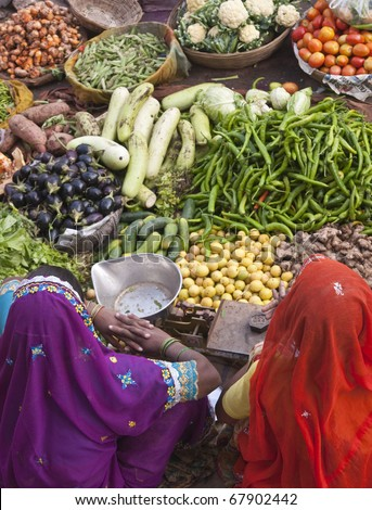 PUSHKAR, INDIA - NOVEMBER 10: Unknown Indian women selling fruit and veg on November 10, 2008 at a street market in Pushkar, Rajasthan, India - stock photo