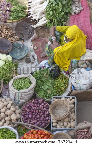 PUSHKAR, INDIA - NOVEMBER 8: Unknown Indian women sells fruit and veg on November 8, 2008 at a street market during the annual Camel Fair in Pushkar, Rajasthan, India - stock photo