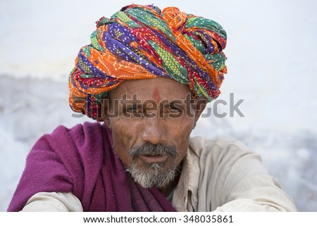 PUSHKAR, INDIA - OCTOBER 25, 2014: Unidentified Indian man, sits on the ghat along the sacred Sarovar lake. Pushkar - famous worship place in India - stock photo