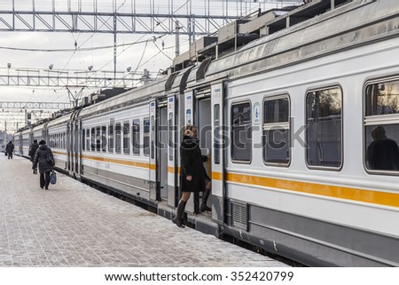 PUSHKINO, RUSSIA, on DECEMBER 17, 2015. Winter day. The suburban electric train stopped at a platform of the railway station. Passengers go on a platform - stock photo