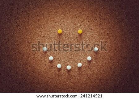 pushpin arrangement on corkboard. smiley face with pushpins on corkboard. - stock photo