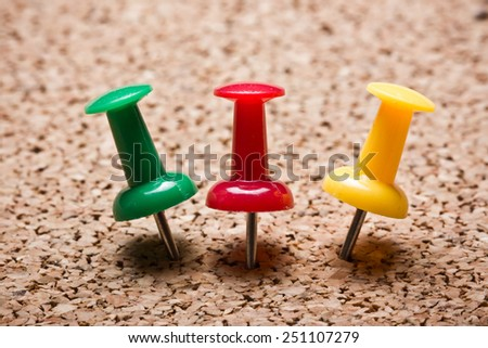 Pushpins attached to cork board. - stock photo