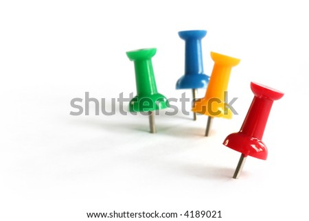 Pushpins in primary colors of red, green, yellow and blue.  Focus on front red pushpin.