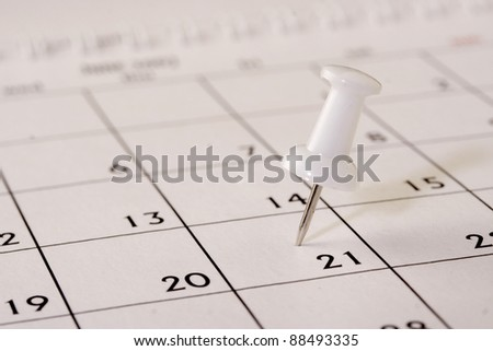 Pushpins on calendar date - stock photo
